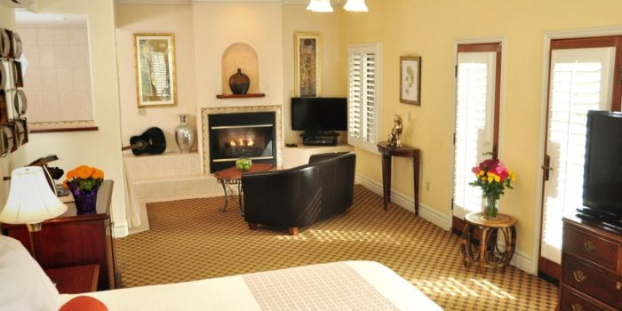 Hotel bedroom showing white bedspread, brown carpet, a fireplace and sofa.