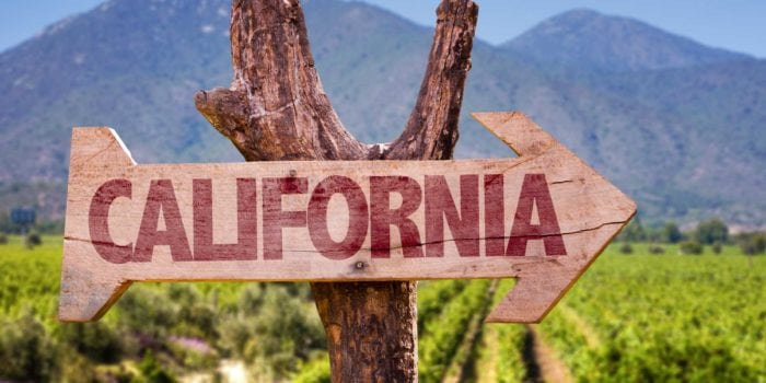A rustic sign pointing toward the right directing you to California. The mountains and vineyards are in the background.