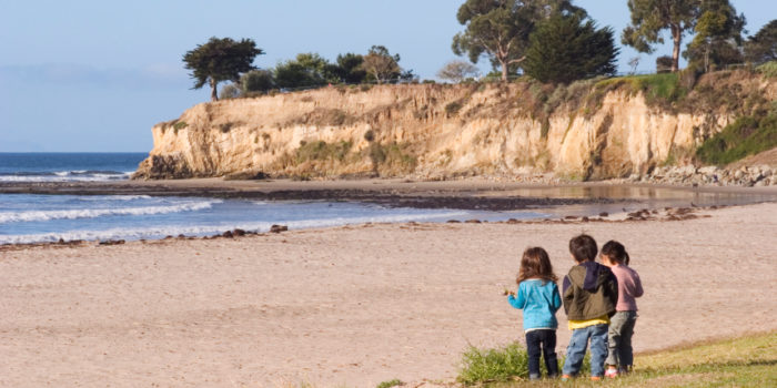 Three youngsters looking at the Pacific coastline and tidepools in Santa Barbara, California.
