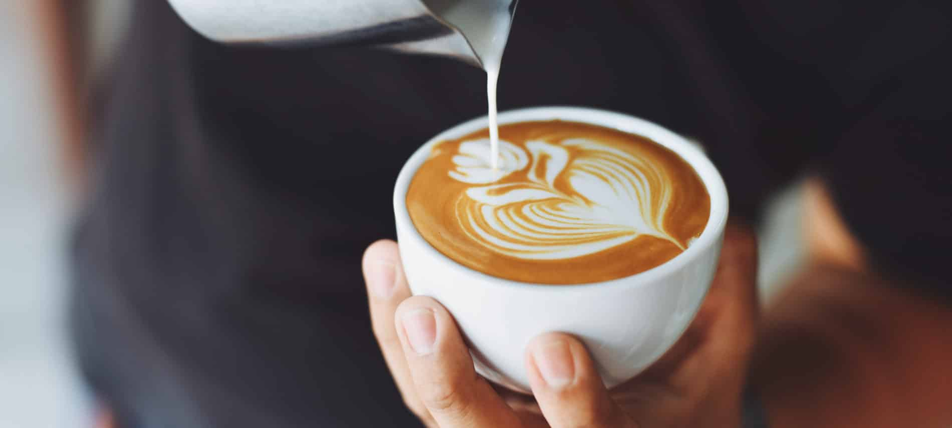 Person pouring milk into a cappuccino