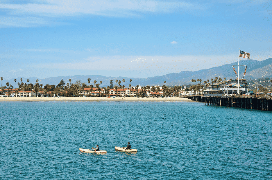 Two people in yellow kayaks in Santa Barbara harbor by West beach amidst distant mountains and blue skies