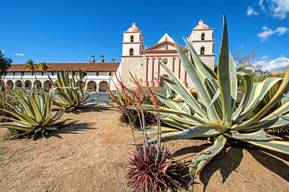 Spanish-style Old Mission in Santa Barbara CA with symmetrical twin towers amidst blue skies