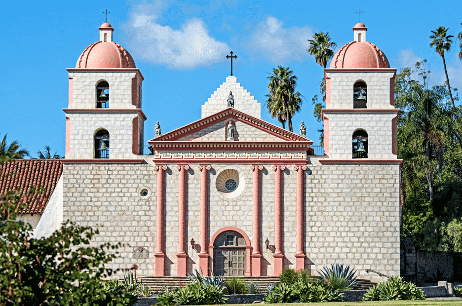 Spanish-style Old Mission in Santa Barbara CA with white and warm pink colors and symmetrical twin towers amidst blue skies