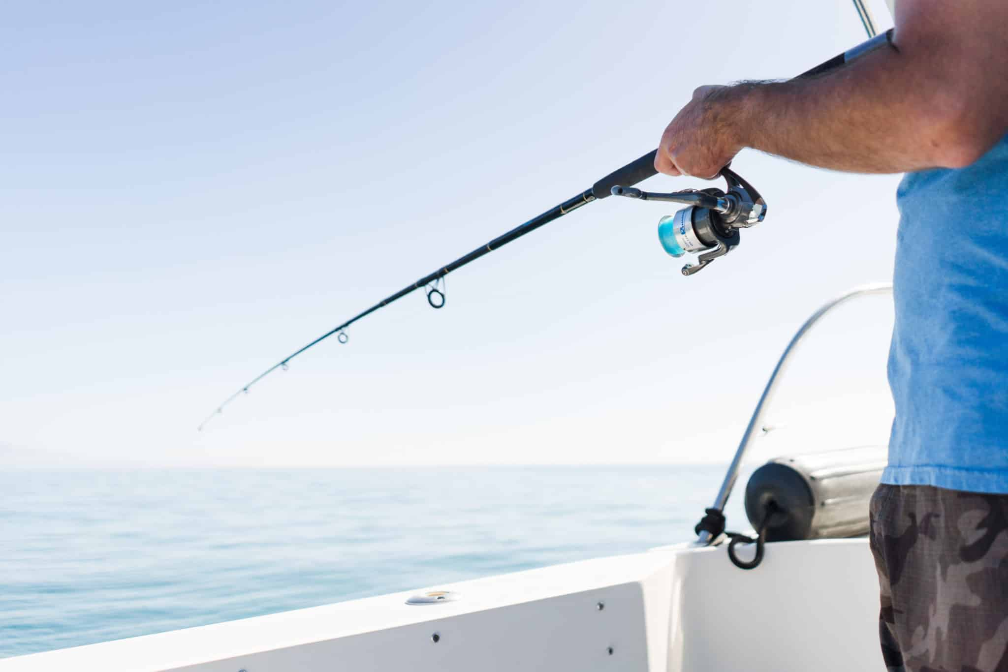 blue sky, darker blue water and hands holding a fishing pole over the side of the boat.