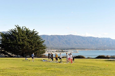 green lawn by water, blue sky, group of people in distance taking an exercise calss