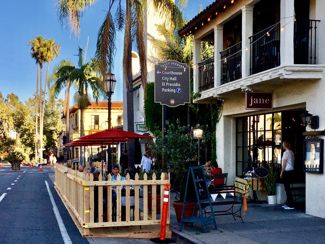 A wooden picket fence extends into State Street so diners sitting under red umbrellas can enjoy the expanded outdoor dining during COVID.