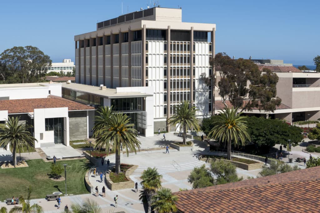 Exterior aerial view of University of California Santa Barbara Library amidst palm trees and blue skies