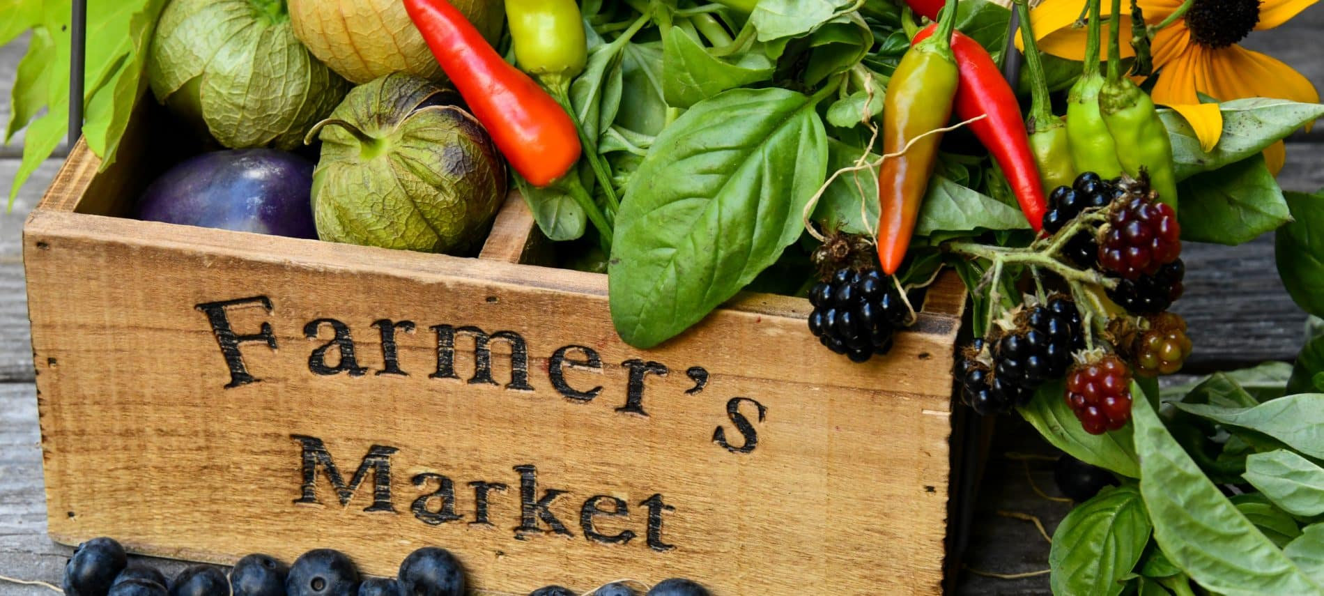 """Wood basket engraved with """"farmers market"""" filled with colorful produce"""
