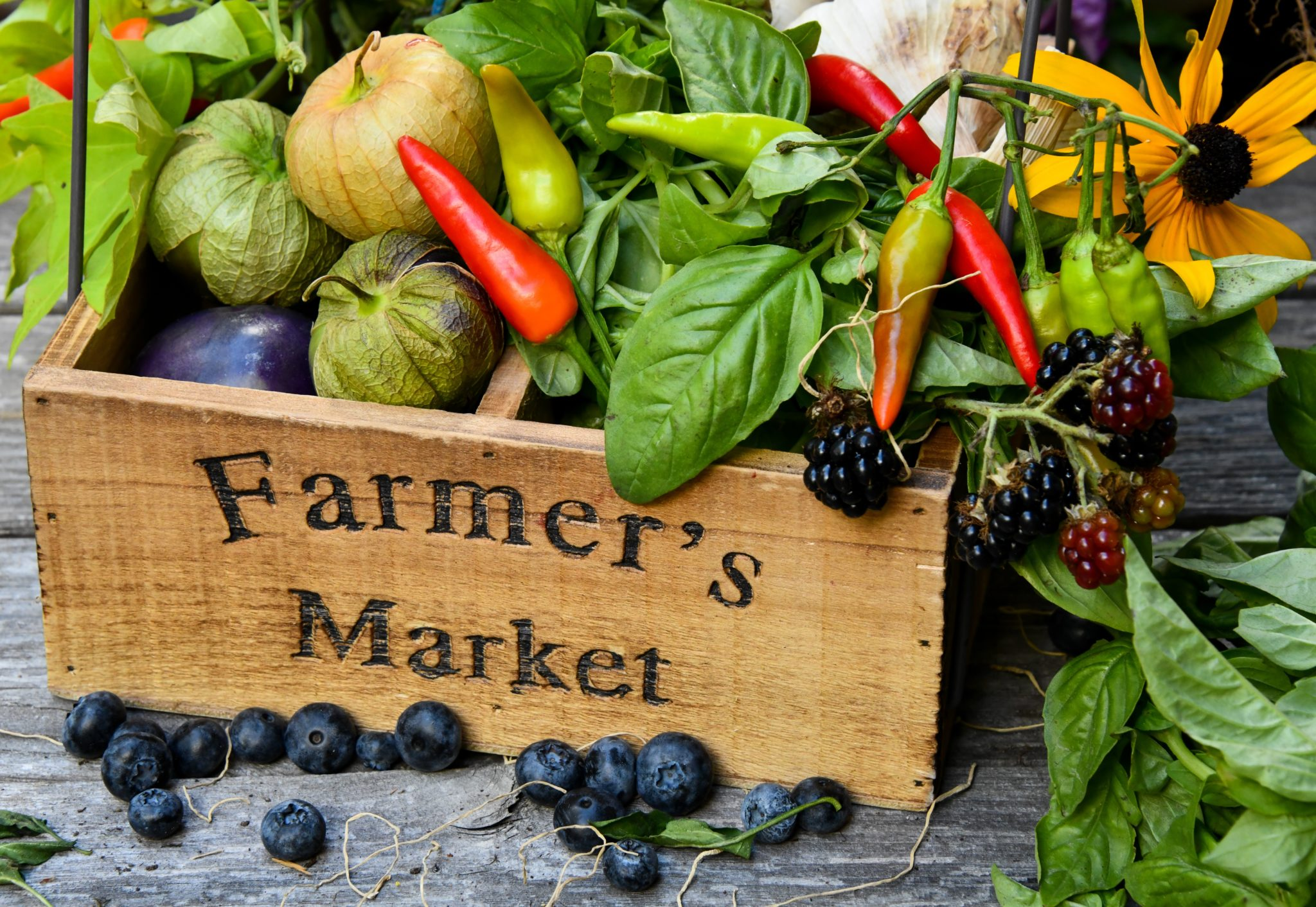 "Wood basket engraved with ""farmers market"" filled with colorful produce"