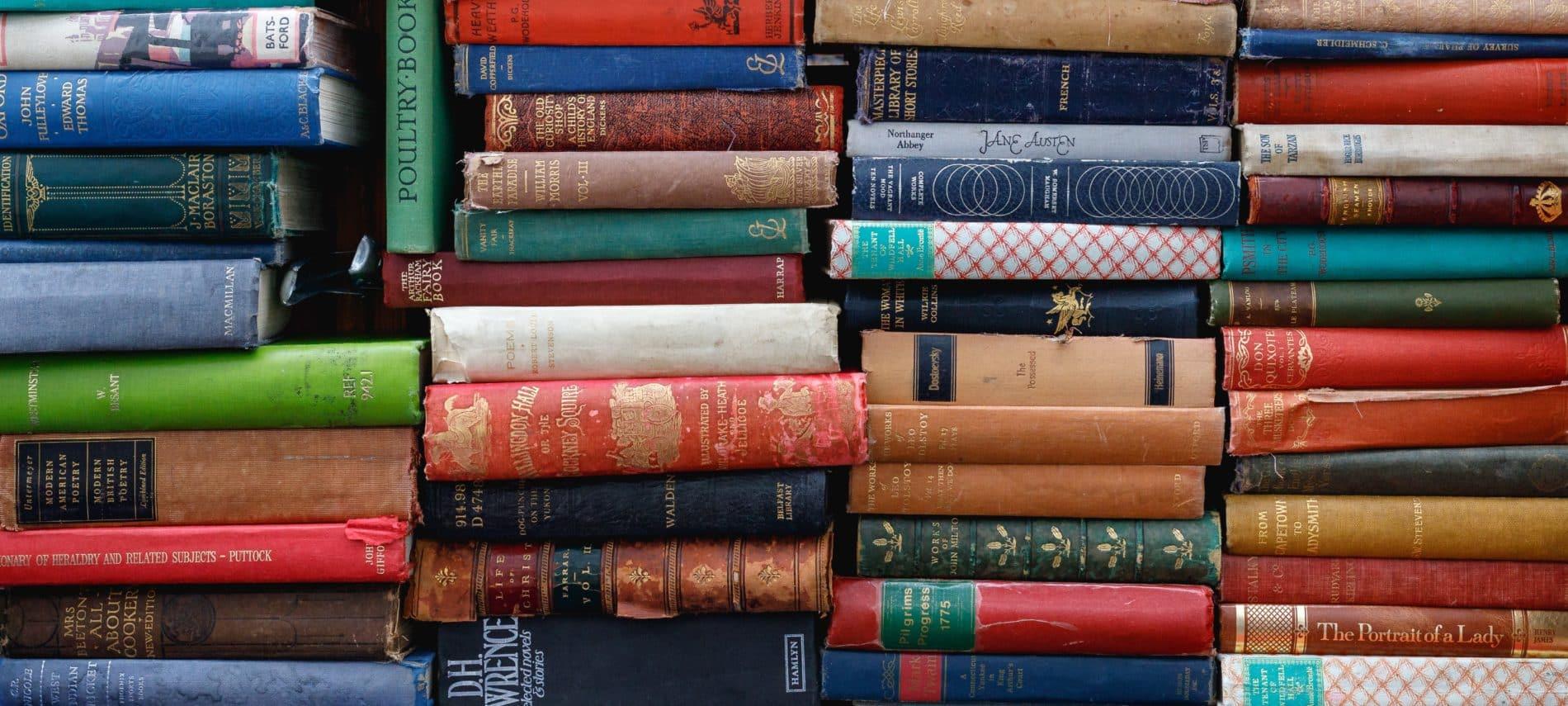 Book shelf full of stacks of books.