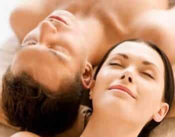 Man and woman laying head to head on table during couples massage