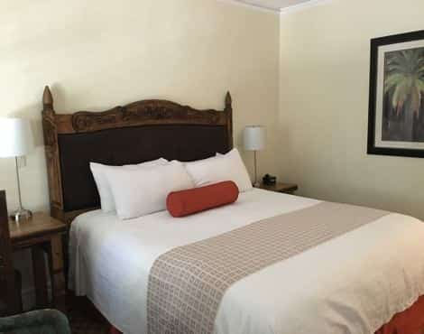 Guest room with ivory wall, wood and leather headboard, white bedding and nightstand with lamp