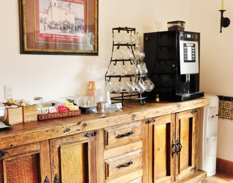 Guest beverage counter in rustic wood with coffee maker, glass mugs, and beverage supplies