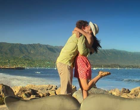 Man and woman embracing on the beach with ocean and mountains in the background