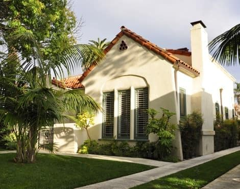 Exterior view of casitas with ivory stucco, red tile roof, green grass and palm trees