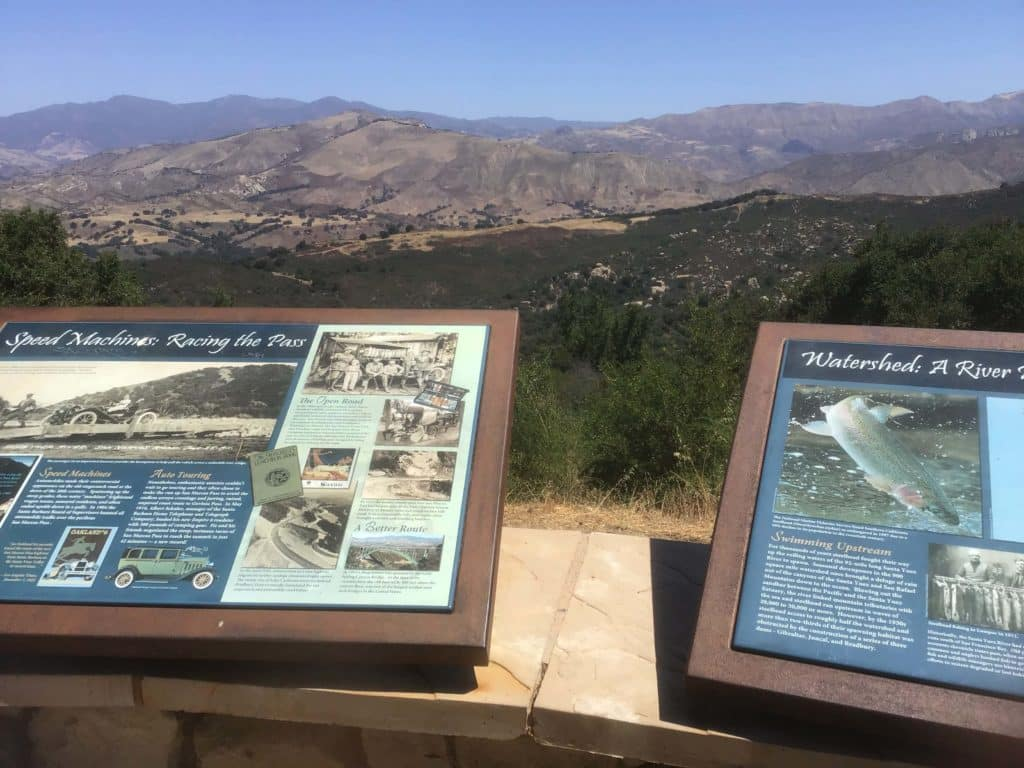 Information boards with historical pictures in front of roadside pullout mountains in the back