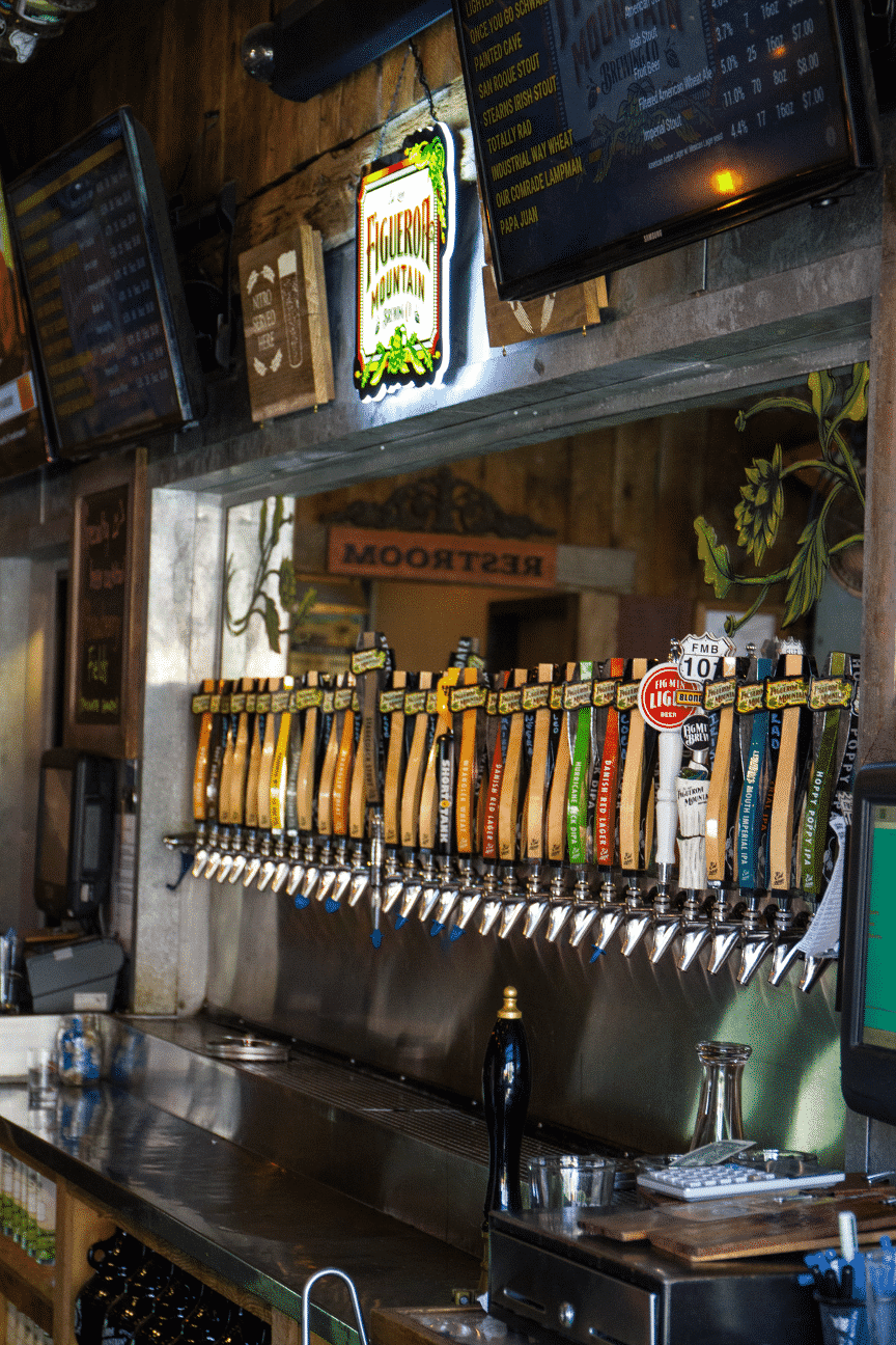 Variety of colorful beer taps at a local bar
