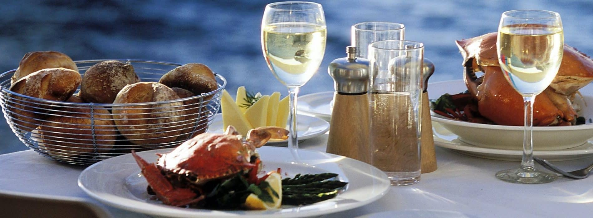 Dining table by the water set with seafood and white wine