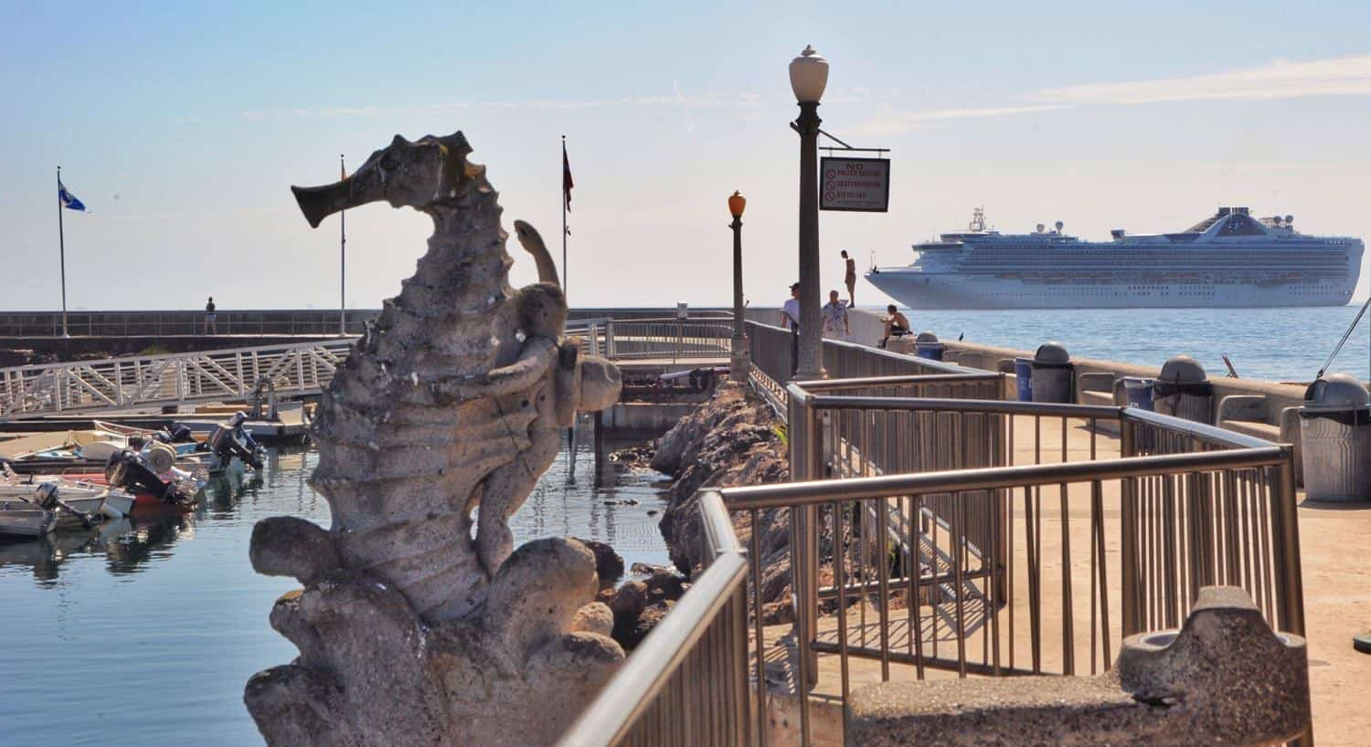 Seahorse sculpture in the harbor with docked boats and a cruise ship in the background
