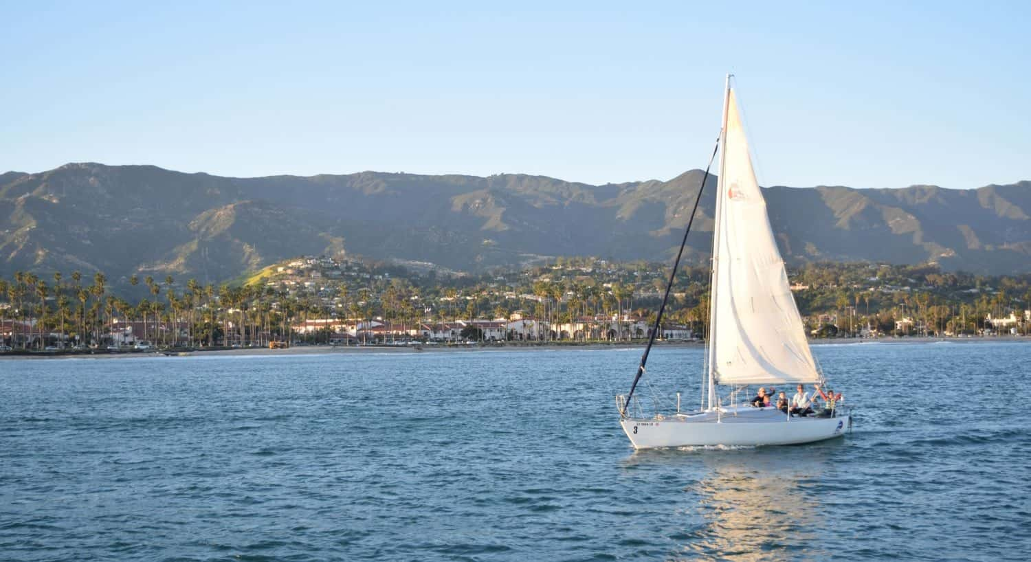 Sailboat sailing in the water with Santa Barbara and mountains in the background