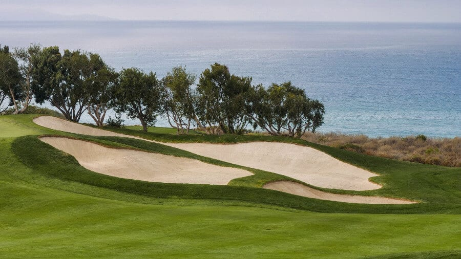 golf course with large sandtraps position along ocean with trees in between