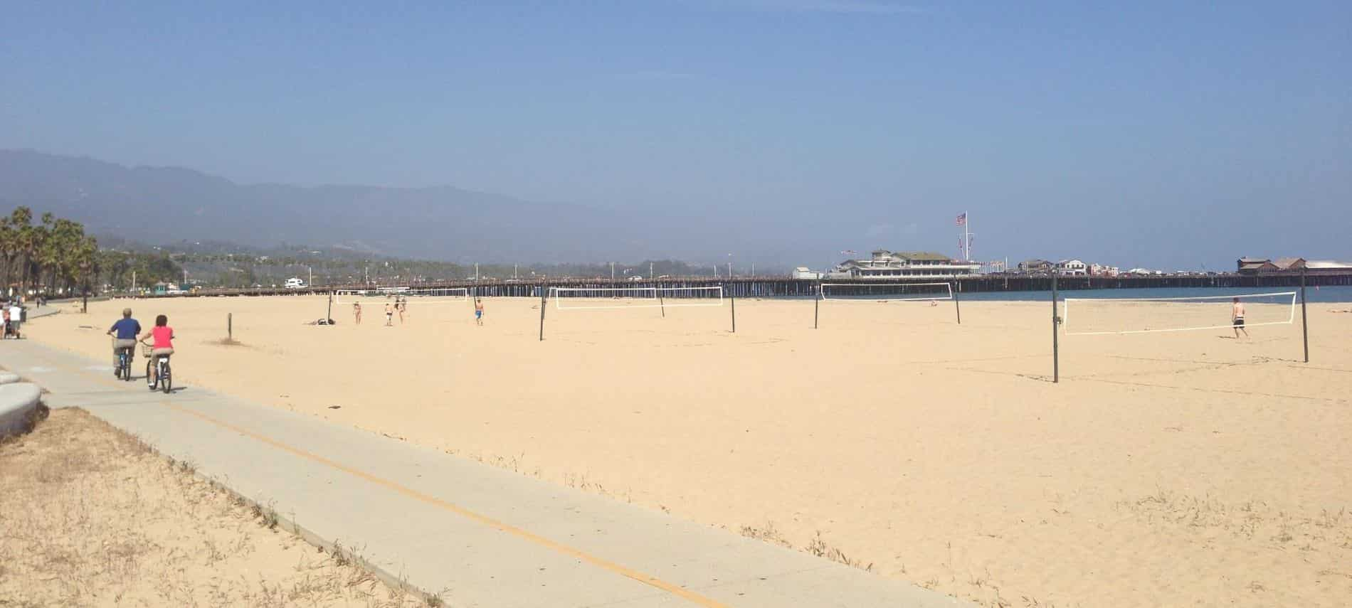 People riding bikes along a sandy beach with volleyball nets surrounded by mountains