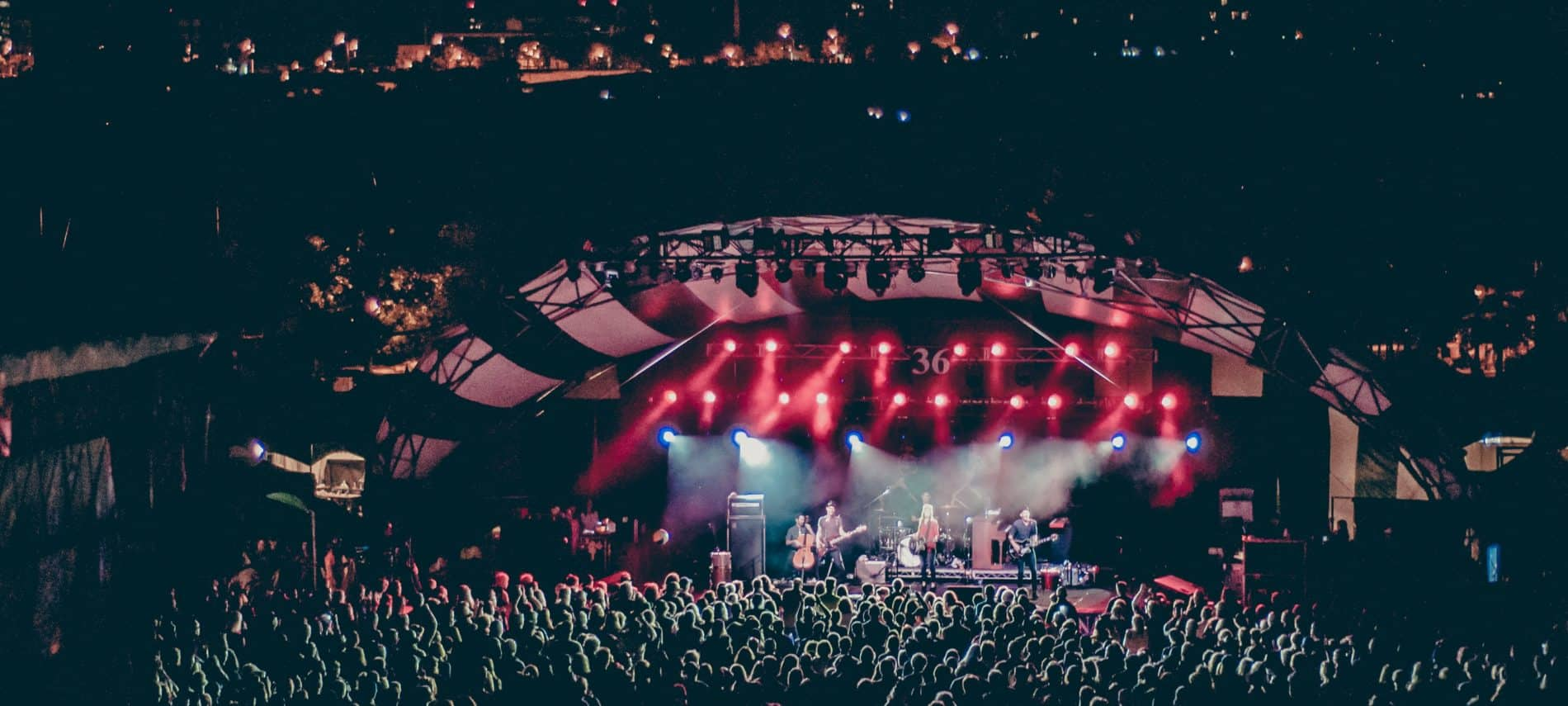Concert venue packed with fans, band on stage with red spotlights