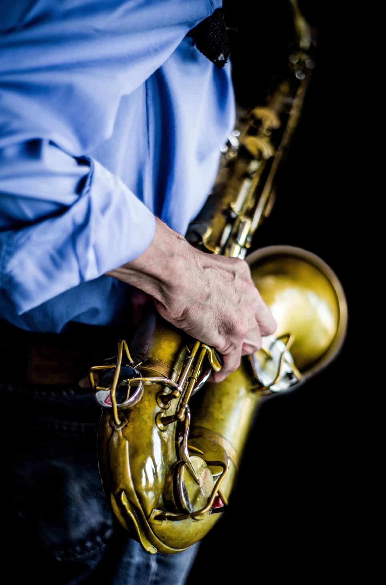 Man in blue shirt playing the saxophone