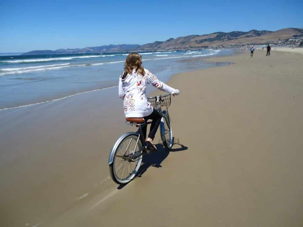 Woman riding her bike on hard-packed sand along the Pacific Ocean