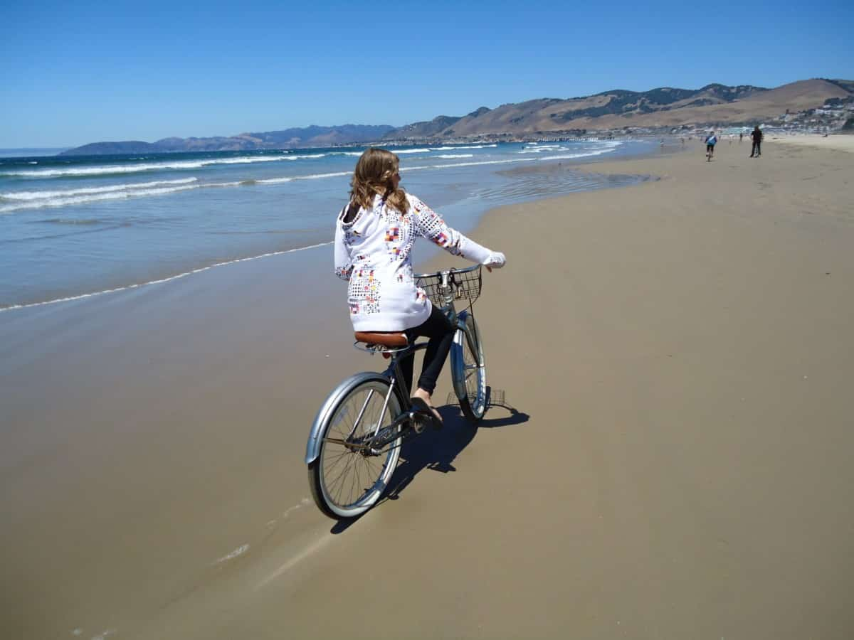Girl riding a bike on the sand-packed beach along the Pacific Ocean with mountains in the distance.