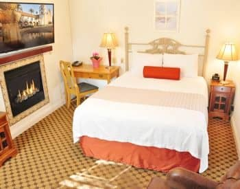 Anacapa guest room with bed, desk with chair, nightstand with lamp and fireplace