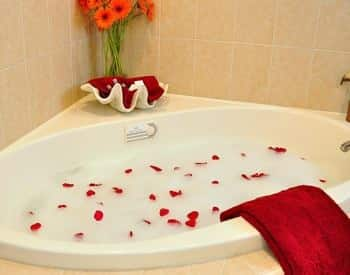 White corner tub with tile surround filled with bubbles and red rose petals