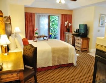 Deluxe king guest room with patio doors, desk with chair, carpeting, and television