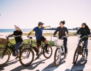 Group of 4 individuals on path sitting on ebike. View of ocean behind the group.