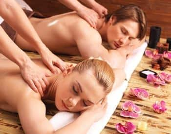 Man and woman lying face down while getting a couples massage