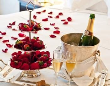 Table topped with red rose petals, three-tiered plates with strawberries, two flutes, and bucket of chilled champagne