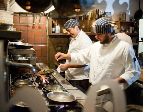 Chefs in white coats and striped hats cooking over a stove in the kitchen