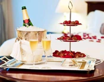 Silver tray on a round table topped with chilled champagne, two full champagne flutes and three tiered try with goodies