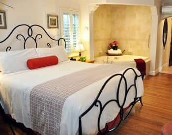 San Clemente guest room with semi-enclosed spa, wood floor, metal scrolled bed and white bedding
