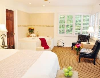 San Miguel guest room with corner windows, carpeting, corner spa, and two sitting chairs
