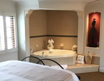 San Nicolas guest room with semi-enclosed corner spa and lit niche with a sculpture