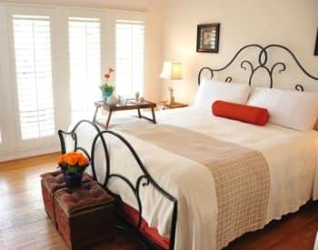 Santa Barbara guest room with scrolled metal bed, white bedding, nightstand with lamp and fresh flowers