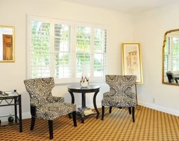 Santa Cruz guest room with ivory walls, carpeting, large window and two sitting chairs