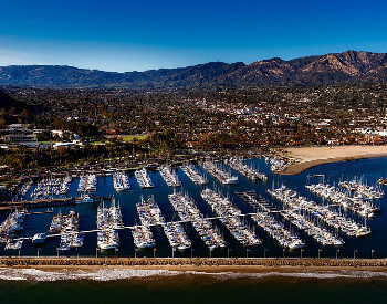 santa barbara harbor with boats anchored with homes and mountains in distance