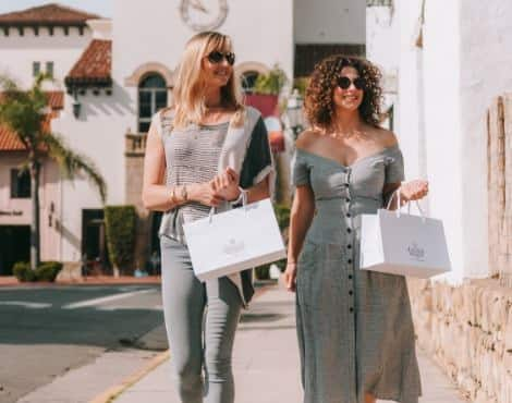Two women walking down a street in Santa Barbara carrying shopping bags