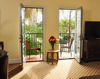 Superior King guest room with two glass doors to the balcony, carpeting, and flat screen TV