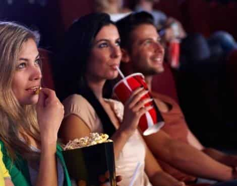 Three people looking up at a theater screen while sipping drinks and eating popcorn