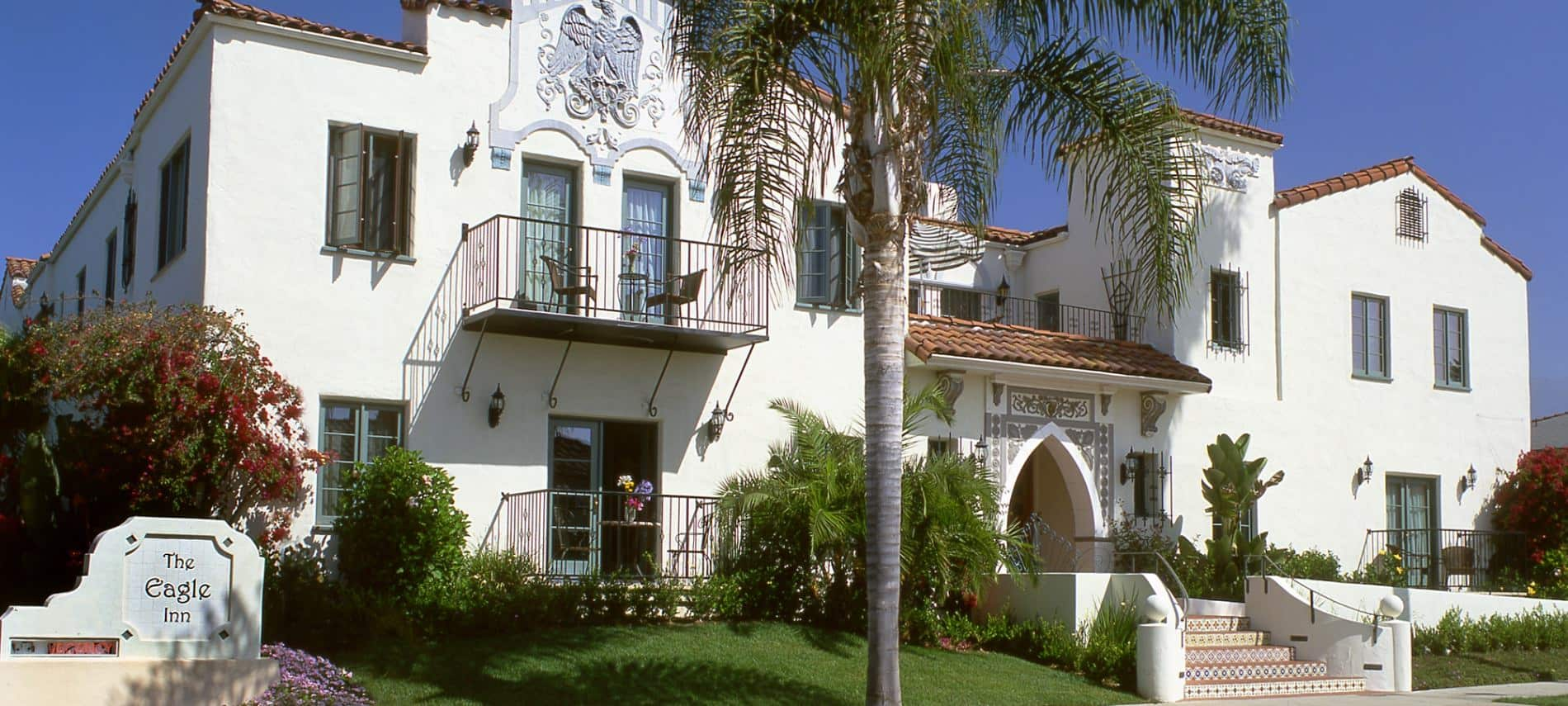 Exterior view of Spanish-style Eagle Inn with palm trees and blue skies