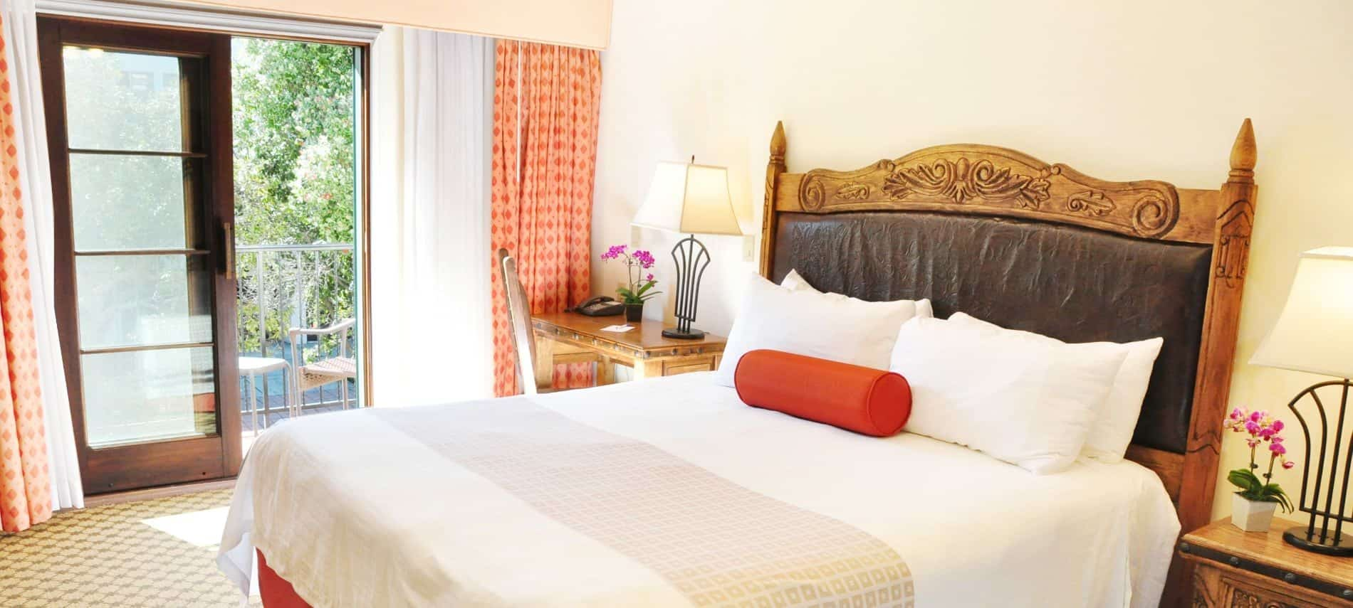 Deluxe king guest room with wood and leather headboard, wood side tables and fresh flowers next to balcony