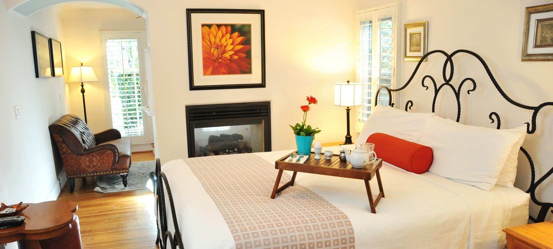 Beautiful San Clemente guest room with iron bed, white bedding, white walls and wood floors